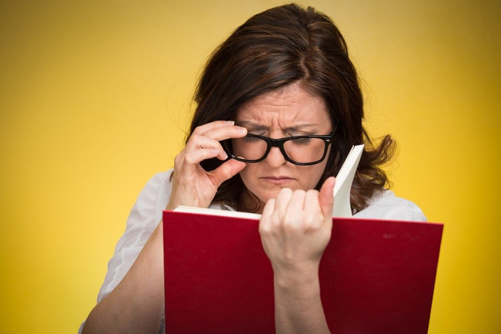 woman with black eye glasses trying to read a book