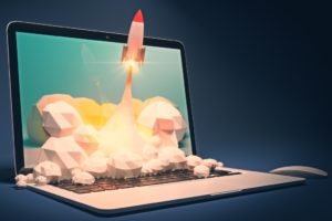 laptop with 3D graphics of rocket taking off popping out of the screen
