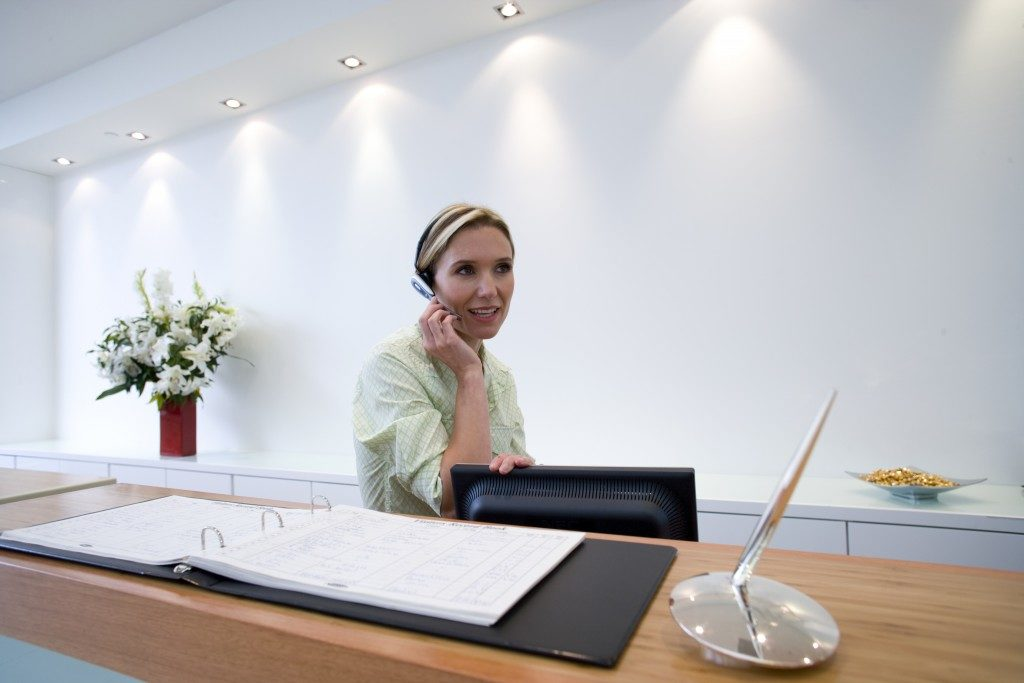 Receptionist behind desk with headset scheduling appointments